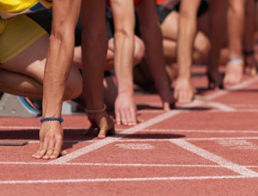 Competitive runners line up at a race starting line.