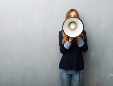 Woman shouting through a megaphone to announce something
